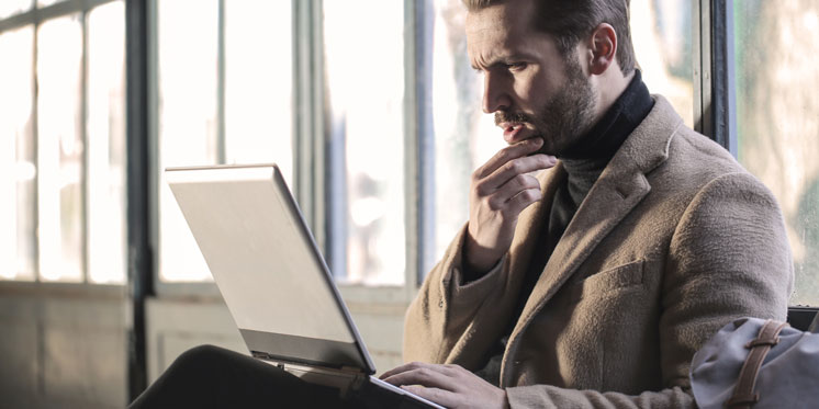 man with concentrated look working on laptop